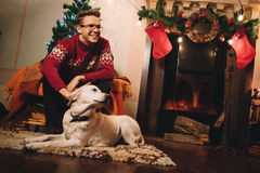 Happy man in red sweater sitting in front of the fireplace royalty free stock photography