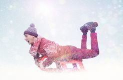 Happy man in a red sweater sledding. Winter, sun, snow, flares. Royalty Free Stock Images