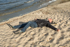 Happy man relaxing on the beach, lying on the sand, smiling, loo Stock Photography