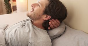 Happy man relaxing in bed. Handsome young man relaxing in bed at home stock footage