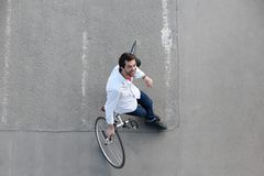 Happy man relaxing with bicycle on street. Top view portrait of a happy man relaxing with bicycle on street Stock Image