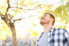 Happy man relaxing breathing deep fresh air in a park royalty free stock photos