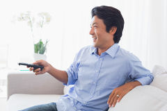 Happy man relaxing on couch watching tv Royalty Free Stock Photos