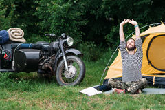 Happy man relaxing in forest on summer morning. Long-awaited trip to nature, motorcycle with sidecar journey alone Royalty Free Stock Photo