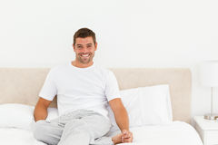 Happy man relaxing on his bed at home Stock Photo