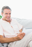 Happy man relaxing on his couch using tablet pc looking at camer Royalty Free Stock Images