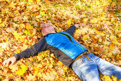 Happy man is relaxing when he is lying on the yellow autumn leav Royalty Free Stock Photos