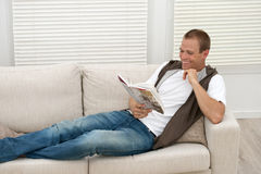 Happy man relaxing on sofa Royalty Free Stock Images