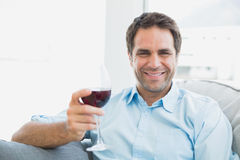 Happy man relaxing on sofa with glass of red wine Stock Images