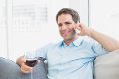 Happy man relaxing on sofa with glass of red wine talking on phone Royalty Free Stock Photos