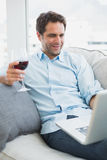 Happy man relaxing on sofa with glass of red wine using laptop Stock Photography