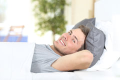 Happy man resting on a bed. Happy man resting on a comfortable bed and looking at camera at home or hotel Stock Photo