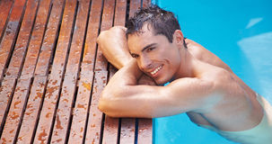 Happy man resting on edge of pool Royalty Free Stock Photography