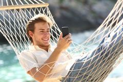 Happy man resting on a hammock using a smart phone. On summer bacation on the beach royalty free stock images