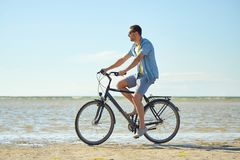 Happy man riding bicycle along summer beach. People, leisure and lifestyle concept - happy young man riding bicycle along summer beach Royalty Free Stock Images