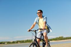 Happy man riding bicycle along summer beach. People, leisure and lifestyle concept - happy young man riding bicycle along summer beach Royalty Free Stock Photos