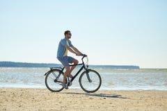Happy man riding bicycle along summer beach Stock Photos