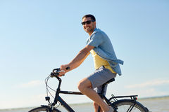 Happy man riding bicycle along summer beach Royalty Free Stock Photos