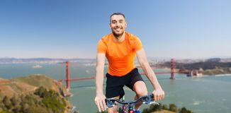 Happy man riding bicycle over golden gate bridge. Fitness, sport and healthy lifestyle concept - happy young man riding bicycle over golden gate bridge in san Stock Image