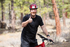 Happy man riding a mountain bike in the woods Stock Images