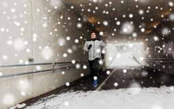 Happy man running along subway tunnel in winter. Fitness, sport, people, season and healthy lifestyle concept - happy young man running along pedestrian subway Stock Photos