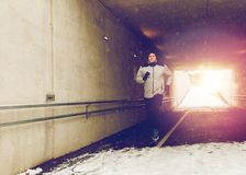 Happy man running along subway tunnel in winter. Fitness, sport, people, season and healthy lifestyle concept - happy young man running along pedestrian subway Royalty Free Stock Photography