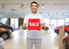 Happy man with sale sigh over auto show background Royalty Free Stock Images