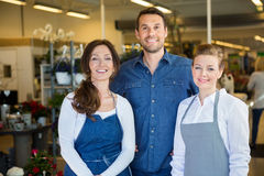 Happy Man With Salesgirls In Flower Shop stock images