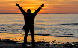 Happy man at sandy beach of the Baltic Sea during sunset Stock Photography
