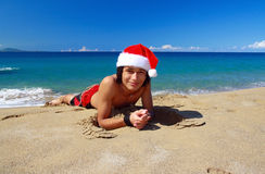 Happy man in santa claus hat on a beach Royalty Free Stock Photography