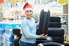 Happy man in Santa hat with gift winter tires in store Christmas Stock Image