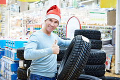 Happy man in Santa hat with gift winter tires in store Christmas Royalty Free Stock Images