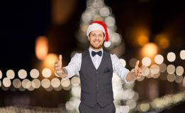 Happy man in santa hat holding something imaginary. Winter holidays and people concept - happy man in santa hat holding something imaginary over christmas tree royalty free stock photo