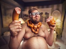 Happy man with sausages. Happy man in glasses with sausages round his neck holds big sausages in both hand sitting in the room stock image