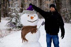 Happy man sculpt a big real snowman. Funny man has fun in winter park, wintertime Stock Image