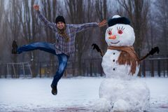 Happy man sculpt a big real snowman. Funny man has fun in winter park, wintertime Stock Images