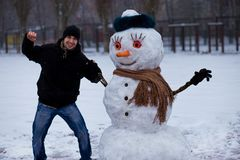 Happy man sculpt a big real snowman. Funny man has fun in winter park, wintertime Stock Photo