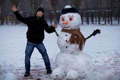 Happy man sculpt a big real snowman. Funny man has fun in winter park, wintertime Royalty Free Stock Photography