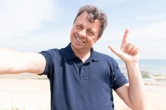 Happy man on sea vacation laughing at beach taking selfie phone stock photos
