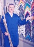 Happy man seller in picture framing studio with wooden details. Happy man seller standing in picture framing studio with wooden details Royalty Free Stock Photo