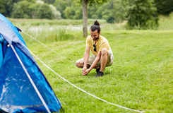 Happy man setting up tent outdoors Royalty Free Stock Image