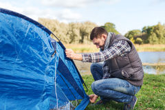 Happy man setting up tent outdoors Stock Image