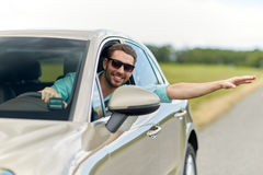 Happy man in shades driving car and waving hand Stock Photography