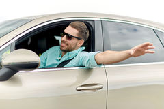 Happy man in shades driving car and waving hand Royalty Free Stock Photography