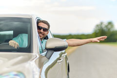 Happy man in shades driving car and waving hand Stock Image