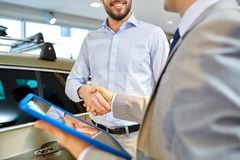 Happy man shaking hands in auto show or salon. Auto business, car sale, deal, gesture and people concept - close up of happy men and car dealer with tablet pc stock image