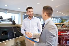 Happy man shaking hands in auto show or salon. Auto business, car sale, technology, gesture and people concept - happy men and car dealer with tablet pc computer royalty free stock photos