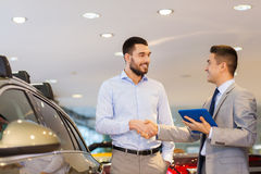 Happy man shaking hands in auto show or salon. Auto business, car sale, technology, gesture and people concept - happy men and car dealer with tablet pc computer stock image