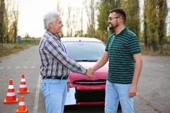 Happy man shaking hands with senior instructor outdoors. royalty free stock photo