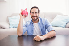 Happy man shaking a pink piggy bank Stock Photos